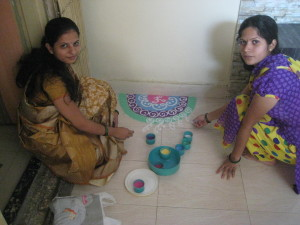 Jyotsna and Nayana create a beautiful rangoli at the entrance to Gokul Kidz for Deepavali.